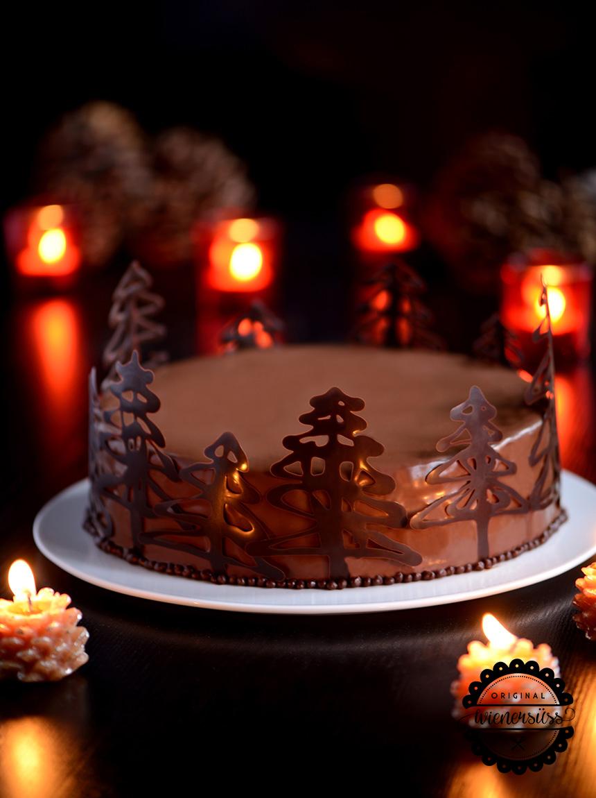 Die Schokoladenmousse-Torte mit Maracujacreme ist mit einer glänzenden Schokoladenglasur überdeckt und weihnachtlich dekoriert. Denn um den Rand der Torte ranken sich kleine Tannenbäumchen aus aufgespritzter Schokolade.
