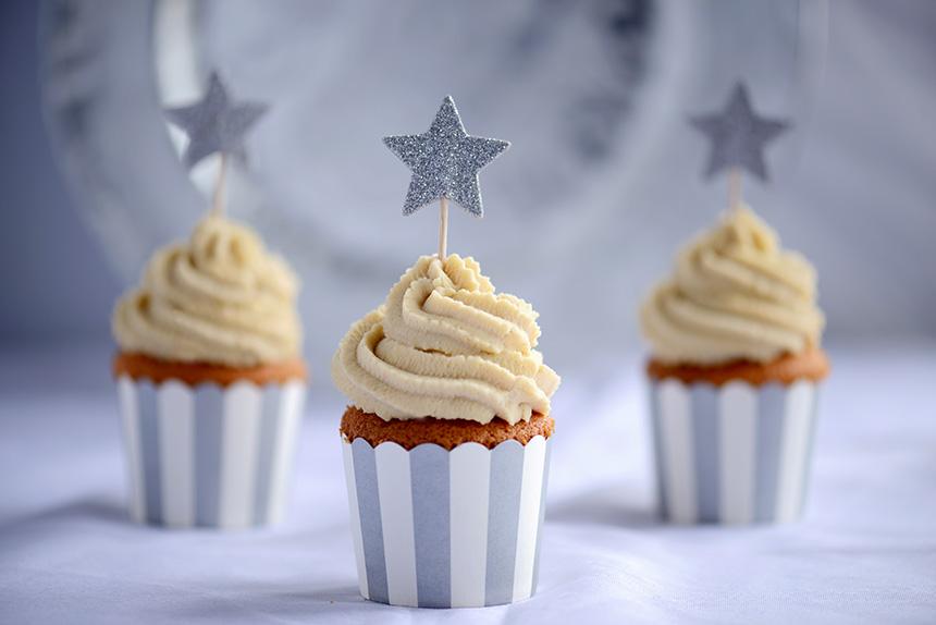 Diese hellen Cupcakes sind mit einer großzügigen Menge Weißer Schokoladen-Topping garniert. Für den silvesterlichen Look habe ich einen silber-weiß gestreiften Cupcake-Wrapper und ein silbernes Glitzersternchen zum Reinstecken verwendet.