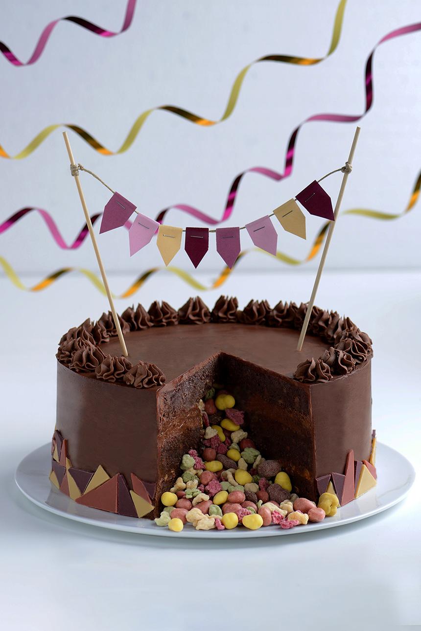 Schneidet man die Brownietorte an, offenbart sich die Überraschung: mitten in der Torte hat sich nämlich ein kunterbunter Kern aus kleinen Leckerein versteckt, die beim ersten Schnitt frech aus der Torte purzeln.