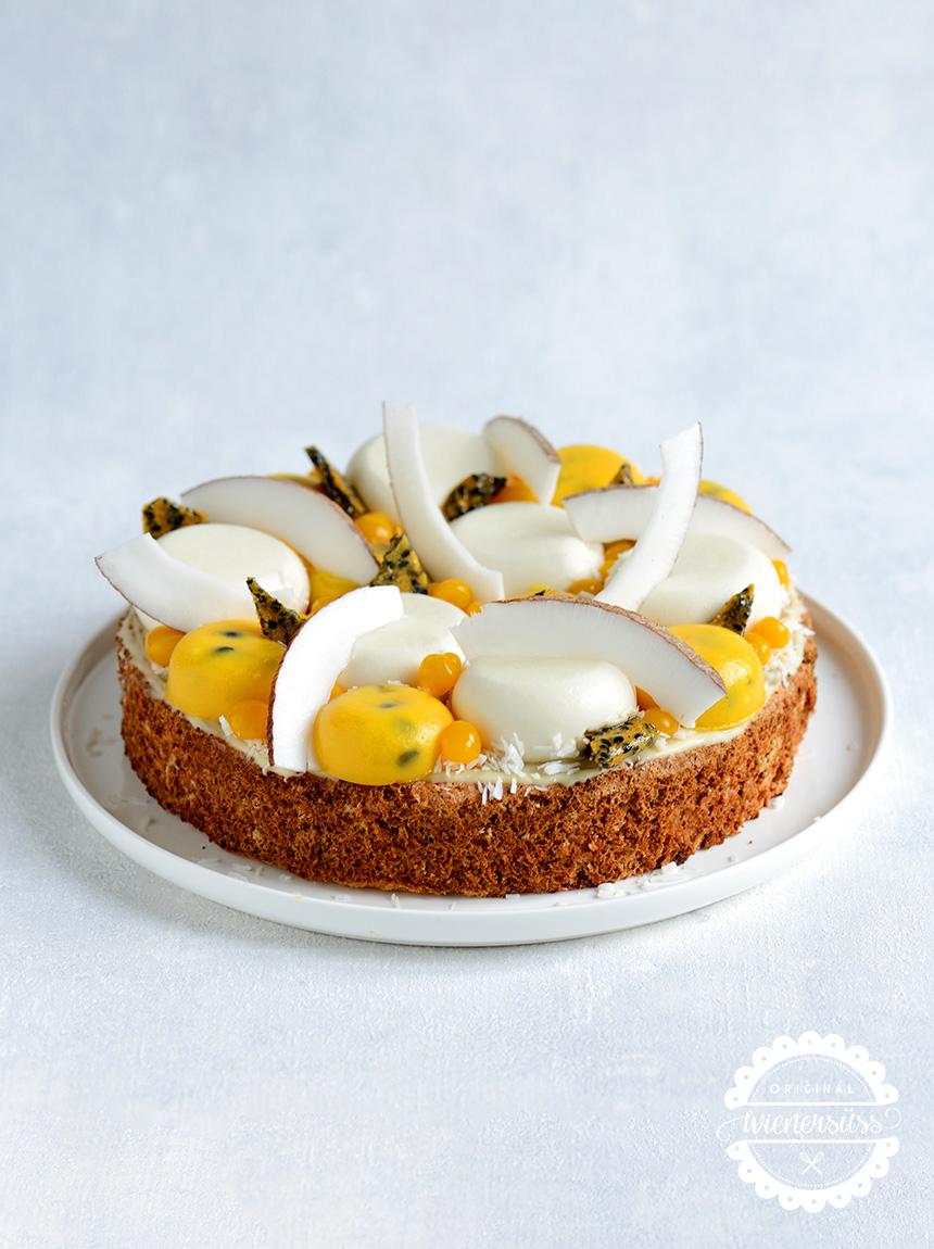 Die Kokos Maracuja Torte gehört wohl zu den eher außergewöhnlichen Torten: Kokos Panna Cotta und Maracujacreme sind nicht bloß übereinandergeschichtet, sondern in Form von Halbkugeln über den Kokostortenboden verteilt. Zusätzlich ist die Torte mit Kokosspalten, Sesam Brittle und Mango Fruchtkaviar-Kügelchen belegt.